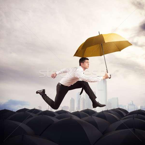 Kitűnik a tömegből tömeg férfi citromsárga esernyő üzlet Stock fotó © alphaspirit