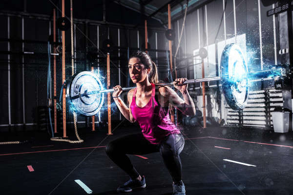 Athletic girl works out at the gym with a barbell with blue energy effects Stock photo © alphaspirit