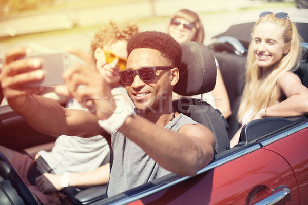 Young friends take a selfie in a cabriolet car Stock photo © alphaspirit