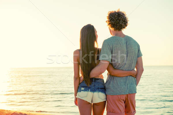 Couples sunrise plage regarder horizon fille Photo stock © alphaspirit