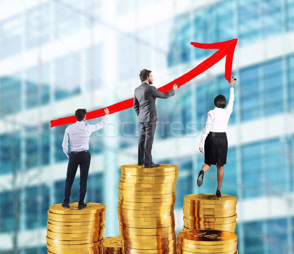 Business team draws growing arrow of company statistics over the piles of money Stock photo © alphaspirit