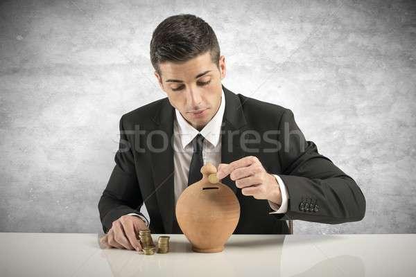 Businessman putting coin into the piggy bank Stock photo © alphaspirit