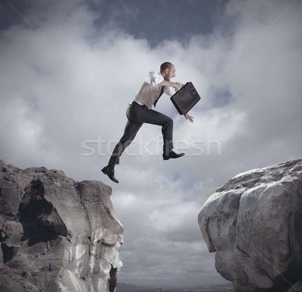 Businessman jumping over the mountains Stock photo © alphaspirit