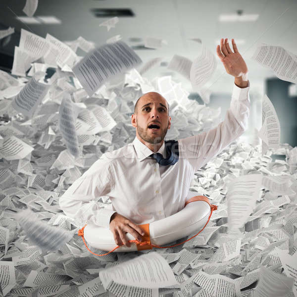 Businessman with lifebuoy sinks between worksheets in office Stock photo © alphaspirit