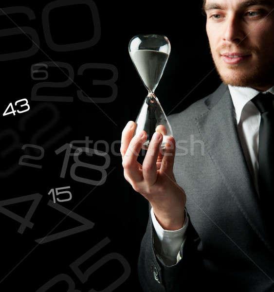 Businessman holding a hourglass Stock photo © alphaspirit