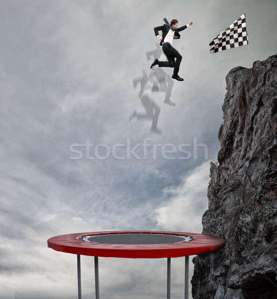 Zakenman springen trampoline bereiken vlag prestatie Stockfoto © alphaspirit