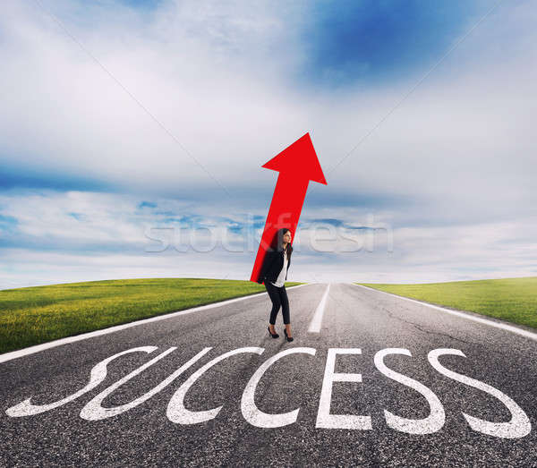 Businesswoman holds a big arrow on a success way. Concept of successful businesswoman and company st Stock photo © alphaspirit