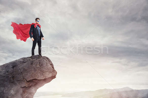 Businessman as a super hero on the peak of a mountain Stock photo © alphaspirit