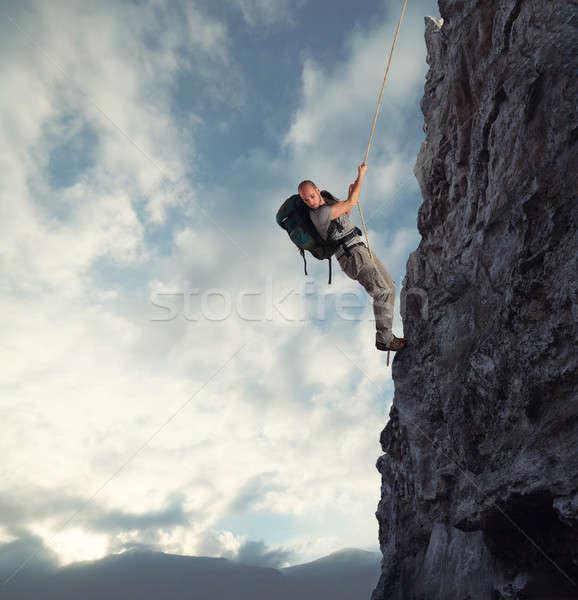 Man climbs a high danger mountain with a rope Stock photo © alphaspirit