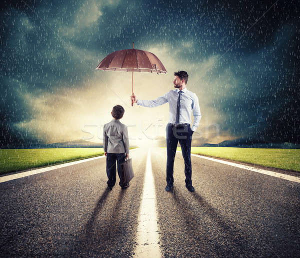 Businessman with umbrella that protect a child. Concept of young economy and startup protection Stock photo © alphaspirit