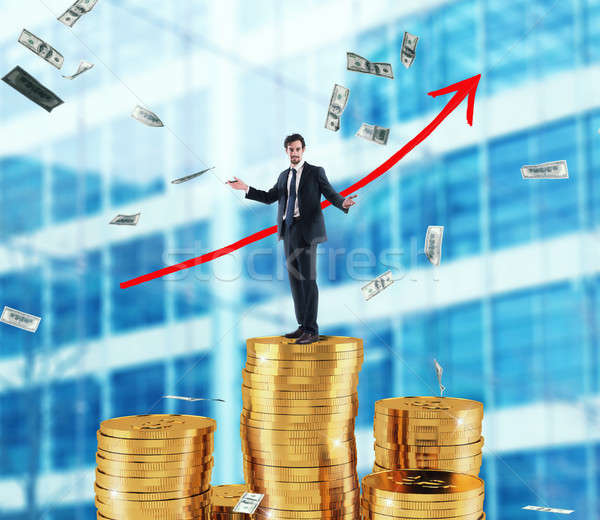 Businessman draws growing arrow of company statistics over a pile of money Stock photo © alphaspirit