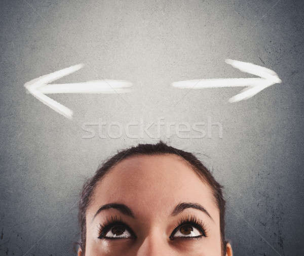 Confused business woman undecided about the right direction to follow Stock photo © alphaspirit