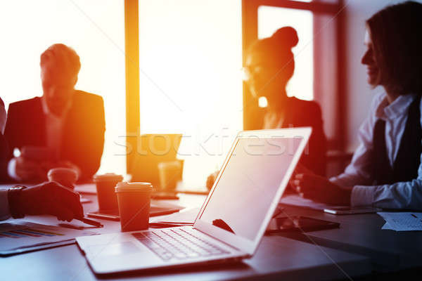 Laptop in an office with businesspeople. Concept of internet sharing and interconnection Stock photo © alphaspirit