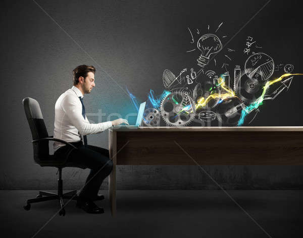 Businessman in a desks works on a creative project Stock photo © alphaspirit