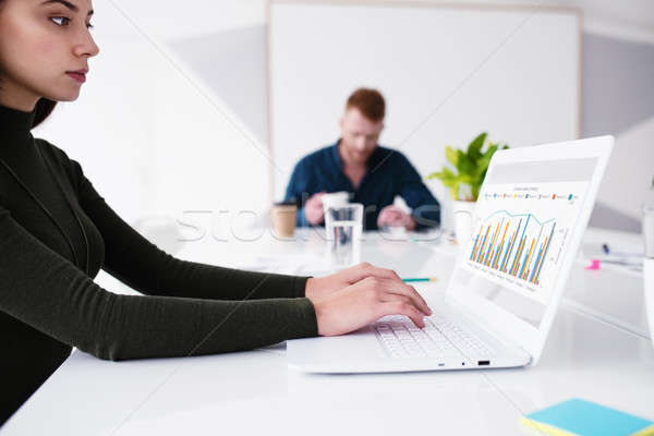 Girl works on a laptop with company statistics. Concept of internet sharing and interconnection Stock photo © alphaspirit