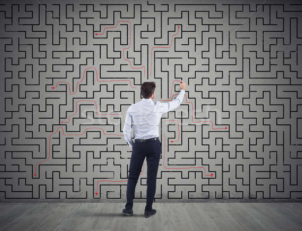 Businessman draws the solution of a labyrinth. Concept of problem solving Stock photo © alphaspirit