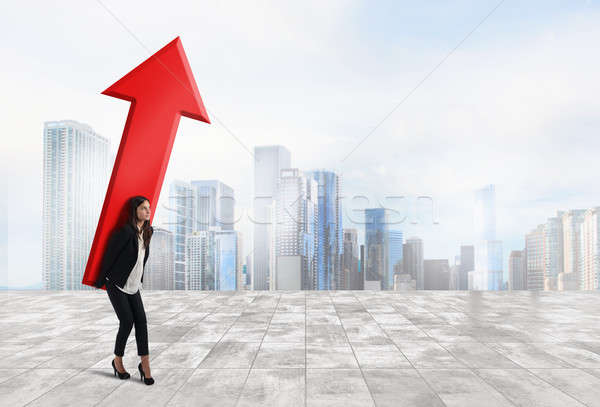 Businesswoman holds a big arrow. Concept of business growth and success Stock photo © alphaspirit