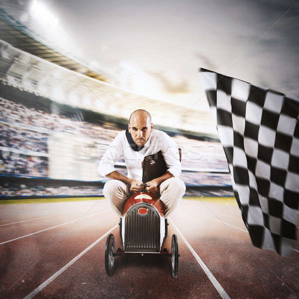 Successful businessman in a small car on the finishing line Stock photo © alphaspirit