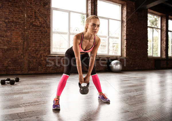 Stock photo: Blonde girl working out at the gym with a kettlebell. crossfit exercise