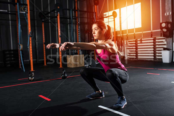 Athletic girl does squat exercises at the gym Stock photo © alphaspirit