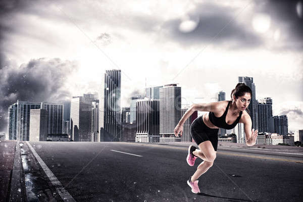 Athletic woman runner on the asphalt of a city road Stock photo © alphaspirit