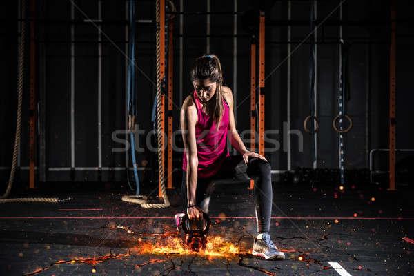 Sportos lány ki tornaterem tüzes kettlebell Stock fotó © alphaspirit
