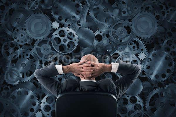 Empresário sessão cadeira assistindo parede Foto stock © alphaspirit