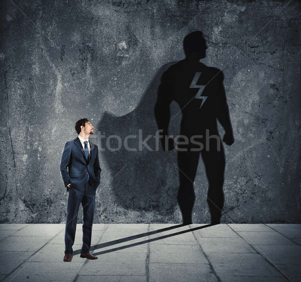 Businessman with his shadow of super hero on the wall. Concept of powerful man Stock photo © alphaspirit