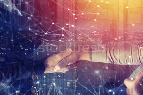 Handshaking business person in office with network effect. concept of teamwork and partnership. doub Stock photo © alphaspirit