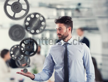 Businessman holds a gear system. Concept of business mechanism Stock photo © alphaspirit