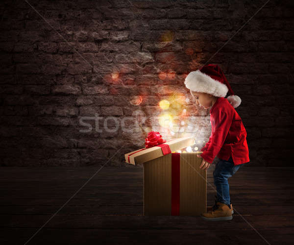 Child that open a magic Christmas gift Stock photo © alphaspirit