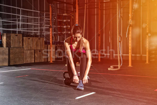 Athletic girl ready to start exercises with a kettlebell at the gym Stock photo © alphaspirit