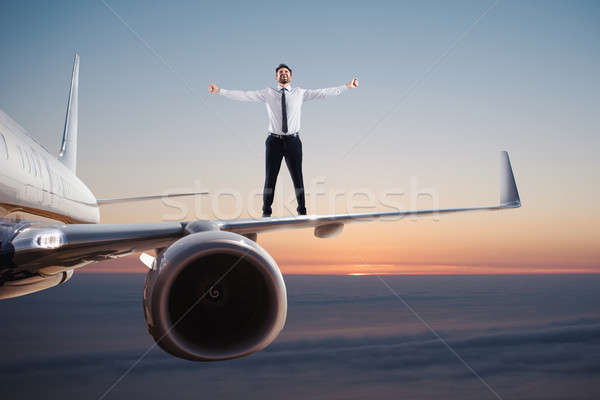 Businessman over an airplane swing. Concept of freedom Stock photo © alphaspirit