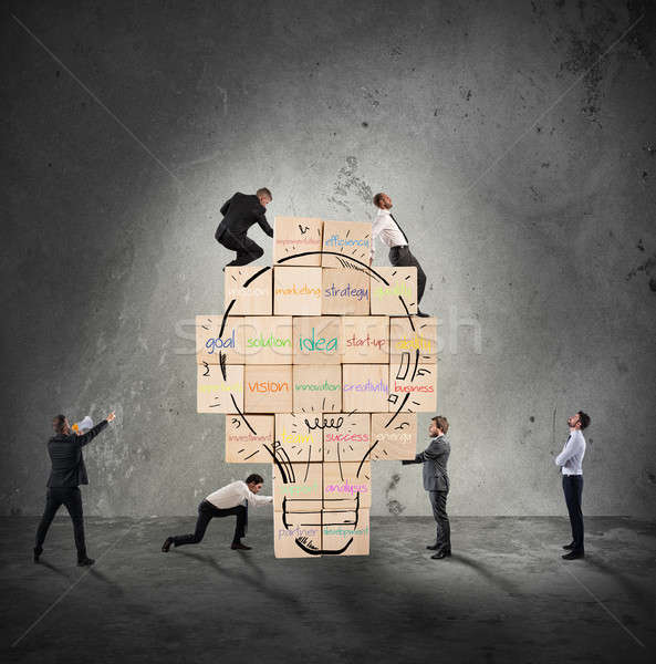 Building a new creative idea. Business person built together a big brick wall with drawn lightbulb Stock photo © alphaspirit