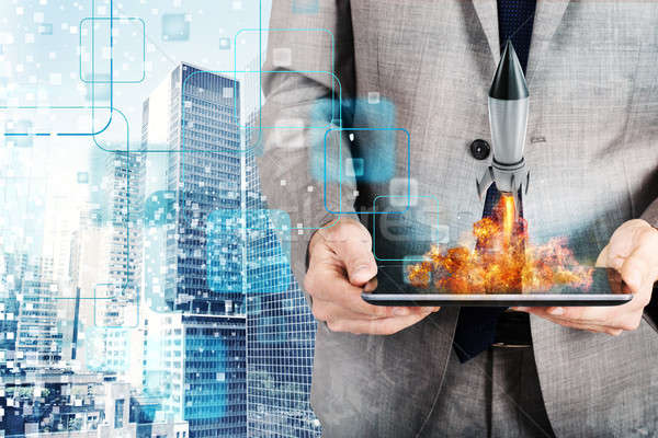 Businessman launches rocket from a tablet. concept of company startup Stock photo © alphaspirit