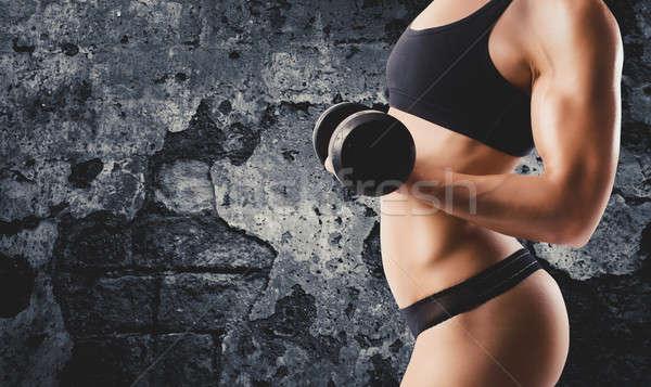 Athletic woman training biceps on grunge background Stock photo © alphaspirit