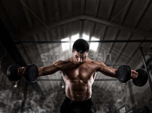 Athletic man training biceps at the gym Stock photo © alphaspirit