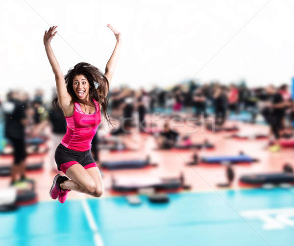 Fitness teacher jumps at the gym Stock photo © alphaspirit