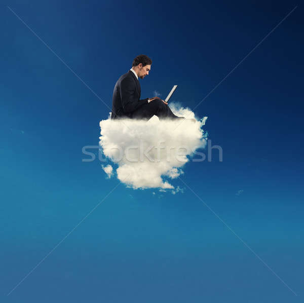 Businessman connected with his laptop over a cloud. concept of social network and internet addiction Stock photo © alphaspirit