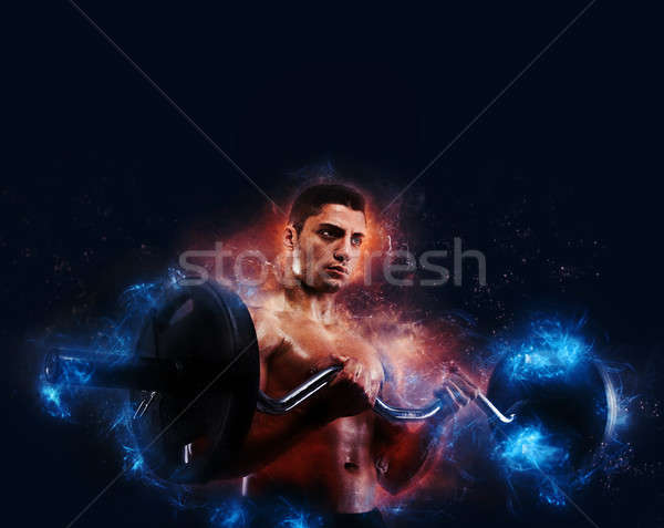 Athletic man training biceps with energy light effect Stock photo © alphaspirit