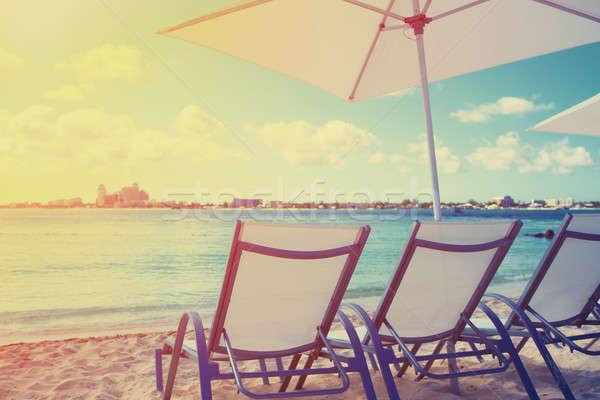 Deck chair on a beautiful beach during sunrise Stock photo © alphaspirit