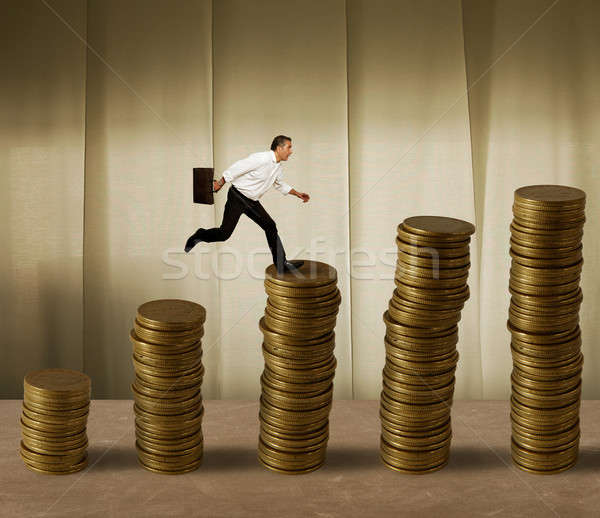 Jumping businessman on money Stock photo © alphaspirit