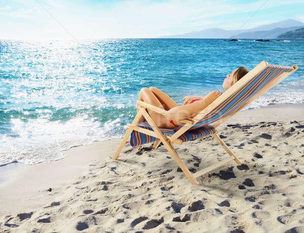 Lány fedélzet szék gyönyörű tengerpart napos Stock fotó © alphaspirit