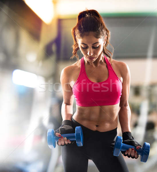 Muscular woman is training at the gym Stock photo © alphaspirit