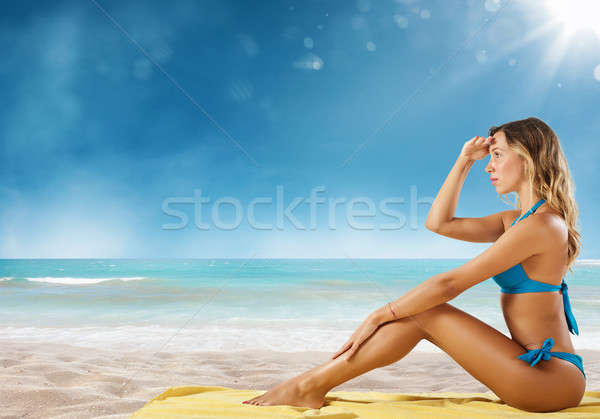 Girl in bikini sits on a beach looking for new travel destination. Stock photo © alphaspirit