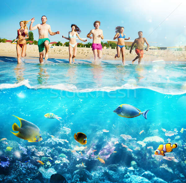 Group of friends run to the sea with colorful fishes. Concept of summertime Stock photo © alphaspirit