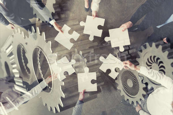 Teamwork of partners. Concept of integration and startup with puzzle pieces and gear overlay. double Stock photo © alphaspirit