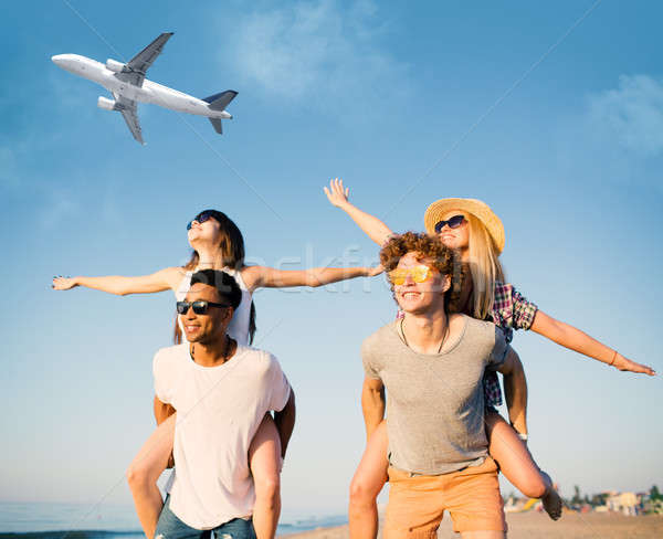 Happy smiling couples playing at the beach with aircraft in the sky Stock photo © alphaspirit