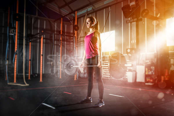 Athletic girl works out at the gym with a barbell Stock photo © alphaspirit