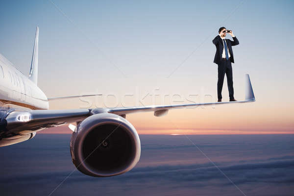Businessman with binoculars over an aircraft searches for new business opportunities Stock photo © alphaspirit